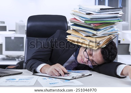 Caucasian businessperson sleeping in the office with documents on his head, shot in the office
