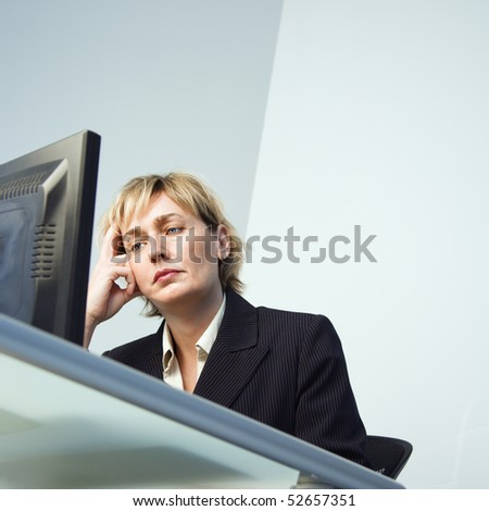 Caucasian businesswoman looking at computer monitor.