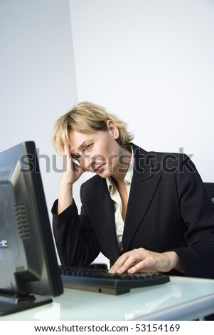 Caucasian businesswoman looking at computer monitor with hand on head looking tired and stressed. - stock photo