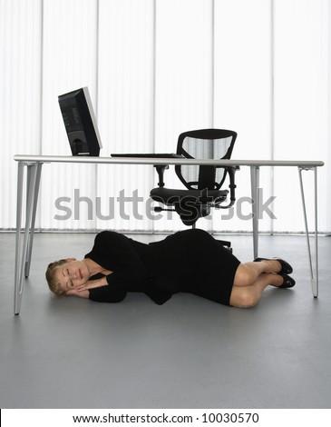 Caucasian Businesswoman Sleeping On Floor Under Computer