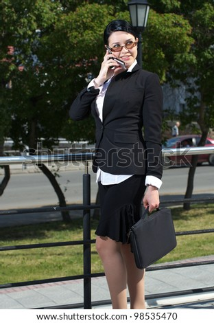 Caucasian businesswoman standing in the street and talking cellphone