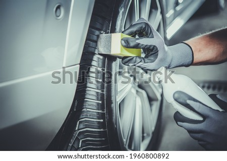 Caucasian Car Detailing Worker Taking Care of Modern Vehicle Tires and Alloy Wheels. Vehicle Detail Cleaning. Automotive Industry Theme. Stock fotó ©