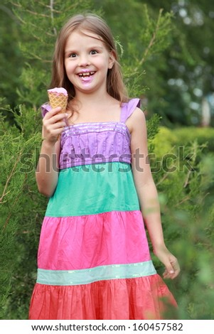 Caucasian charming little girl eats ice-cream smiling and laughing in the park on a summer background of green trees