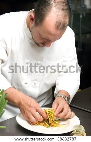 Caucasian chef putting food on a plate in a restaurant kitchen.