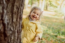 Caucasian child girl playing hide and seek in the park in autumn.