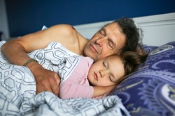 Caucasian child girl sleeping next to dad, grandfather. concept of fatherhood and child care, divorced father and loner. Father hugs daughter who came to sleep with her parents. Blue bedding.