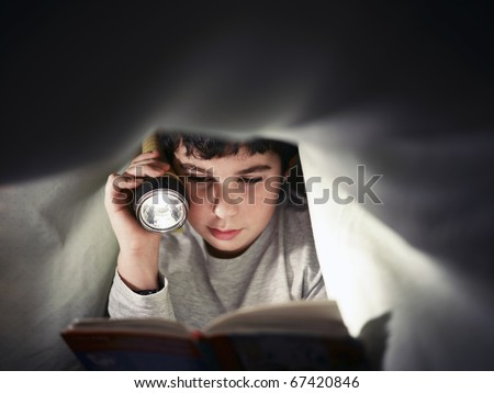 caucasian child reading book under the covers at night. Front view, copy space - stock photo