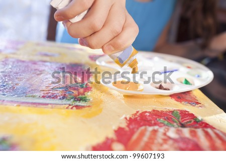 caucasian child's hand puts yellow color to the palette - stock photo