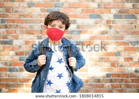 Caucasian child with school bag walking on the street. He is wearing a face mask. Back to school after covid-19 quarantine and lockdown. Foto stock ©