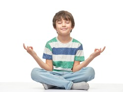 Caucasian children boy in a t-shirt doing yoga, isolated over the white background.