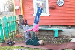 Caucasian children do acrobatic exercise on a track in a village near a wooden house. Boy lies on his back and supports a little girl who stands upside down. Training on self-isolation, a new reality.