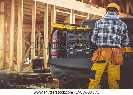 Caucasian Construction Contractor in His 40s and His Modern Black Pickup Truck. Men Preparing His Tools For the Job. Wooden House Skeleton in Background.