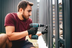 Caucasian construction man working with cordless electrical screwdriver on metal fence