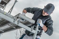 Caucasian Construction Worker Installing Scaffolding Elements.