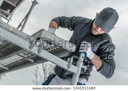 Caucasian Construction Worker Installing Scaffolding Elements.  Сток-фото ©