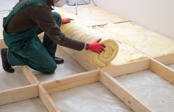 Caucasian Construction Worker with Roll of Insulating Material, Floor Insulating by Mineral Wool.