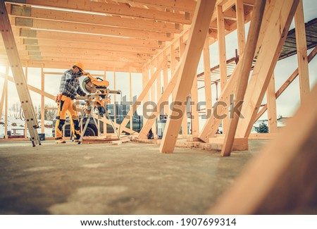 Caucasian Contractor Carpenter Worker in His 40s Using Commercial Grade Circular Saw in Construction Zone. Industrial Theme. Wooden Skeleton Framing Building.