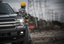 Caucasian Contractor Field Work Job. Worker and His Pickup Truck. Countryside Remote Location with High Voltage Poles in the Background.