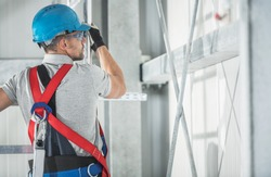 Caucasian Contractor Worker in His 40s Inside Commercial Building Wearing Safety Harness Equipment. Safety at Work Industrial Theme.