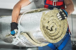 Caucasian Contractor Worker in His 40s with Roll of Mineral Wool Insulation in His Hands Preparing For Commercial Building Walls Insulation.