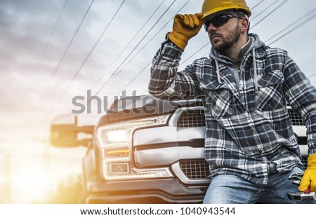 Caucasian Contractor Worker in Yellow Hard Hat and Yellow Safety Gloves in Front of His Pickup Truck. Construction Theme.