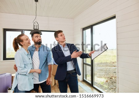 Caucasian couple and caucasian realtor wear blue jacket in new house for further purchase. He tell about house #1516669973