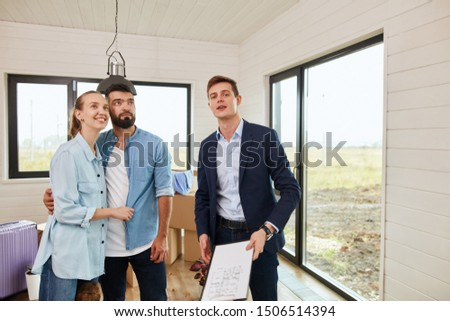 Caucasian couple and caucasian realtor wear blue jacket inspect new house for further purchase #1506514394