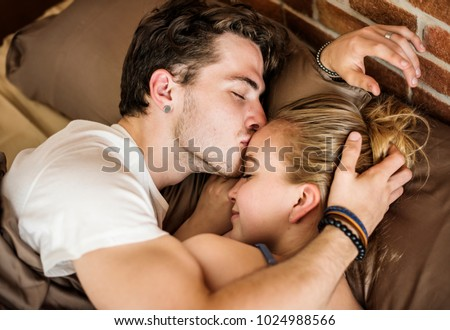 Caucasian couple lying on bed together