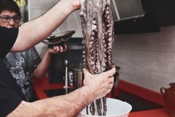 Caucasian couple ready to cook a octopus. Man and woman cooking Galician octopus style.