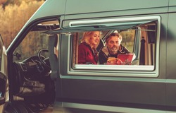 Caucasian Couple Watching Movie Online Inside Their Modern Camper Van During Their Weekend Getaway. Recreational Vehicle RV and Camping Theme.