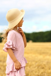 Caucasian cute girl in a wicker hat and a pink blue dress  standing on the  mown wheat field. Agriculture. Rest in the village. Organic food and healthy lifestyle concept