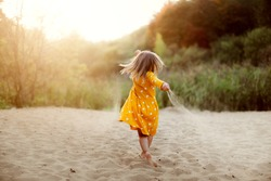 Caucasian cute little girl in yellow dress dancing on the sand in summer at sunset, happy childhood and freedom