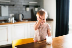 Caucasian cute toddler child with a glass of yogurt and cookies on a chair in a room in a real interior, funny grimy dirty children and healthy food, snack