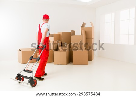 caucasian deliveryman in red uniform holding hand truck, getting ready to load cardboard boxes