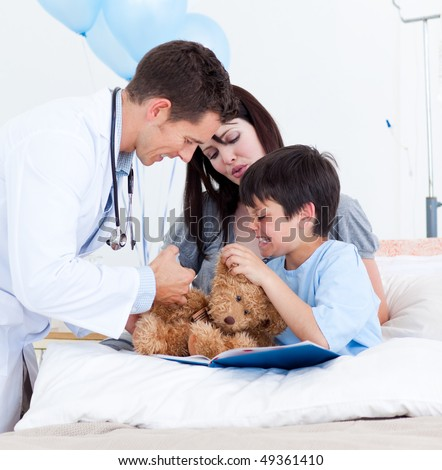 Caucasian doctor playing with a little boy and his mother at the hospital