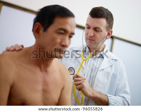 caucasian doctor working and visiting old asian male patient in hospital with stethoscope - stock photo
