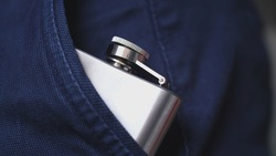 Caucasian Drinking Man Pulling Out and Putting In Shiny Metal Hip Flask of Whiskey Alcohol Concealed in Trousers Pocket