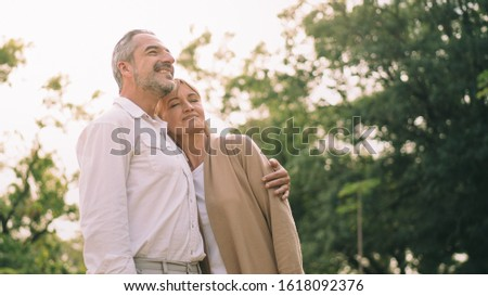 Caucasian elderly couple is standing, holds each other and smiling upward enjoy spending time together with happiness, a happily married couple, carefree retirement lifestyle, love and cherish couple.