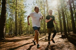 Caucasian elderly father and active son running in forest determined to exercise