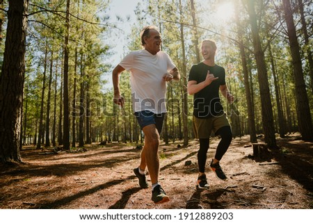 Caucasian elderly father and active son running in forest determined to exercise  Foto stock ©