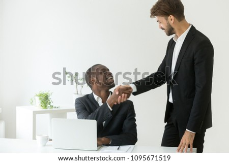 Caucasian employer congratulating handshaking African American subordinate worker with new job position, work promotion, winning project, developing successful business strategy. Concept of leadership