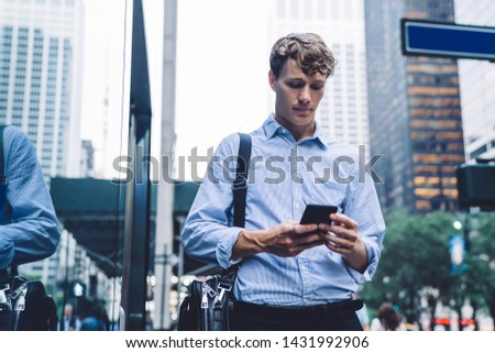 Caucasian employer searching information on smartphone with 4g wireless for browsing internet, intelligent male business trader chatting on cellular gadget while spending day in financial district
