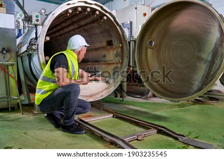 Caucasian Engineer check inside of boiler machine for saefty in production system of beverage industry factory Foto stock ©