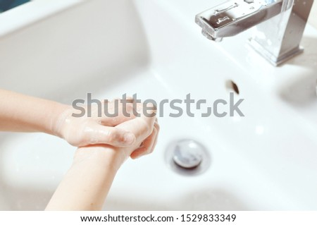 Caucasian (European, white) girl (child, kid) cleaning hands with soap over the sink.