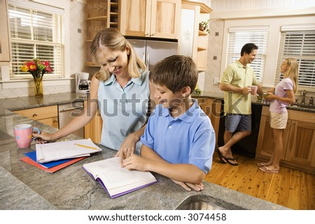 Caucasian family in kitchen doing homework and chatting. - stock photo