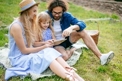 caucasian family using digital tablet during picnic at countryside