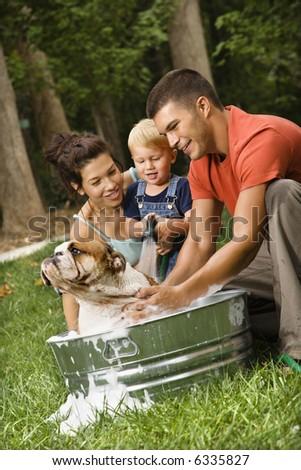 Caucasian family with toddler son giving  English Bulldog a bath outdoors.