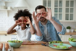 Caucasian father African daughter cooking, family having fun play together while preparing vegetable salad, covering eyes with red paprika circles looking like eyewear. Lifestyle, cookery, joy concept