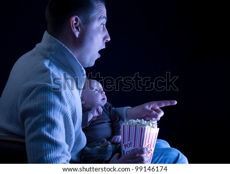 Caucasian   father and son watching a movie on tv and eating popcorn
