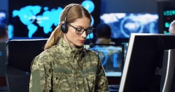 Caucasian female army officer in glasses and headset talking, working on computer in analytic secret base in military. Woman militarian official typing in dark office. Digital support Warfare operator